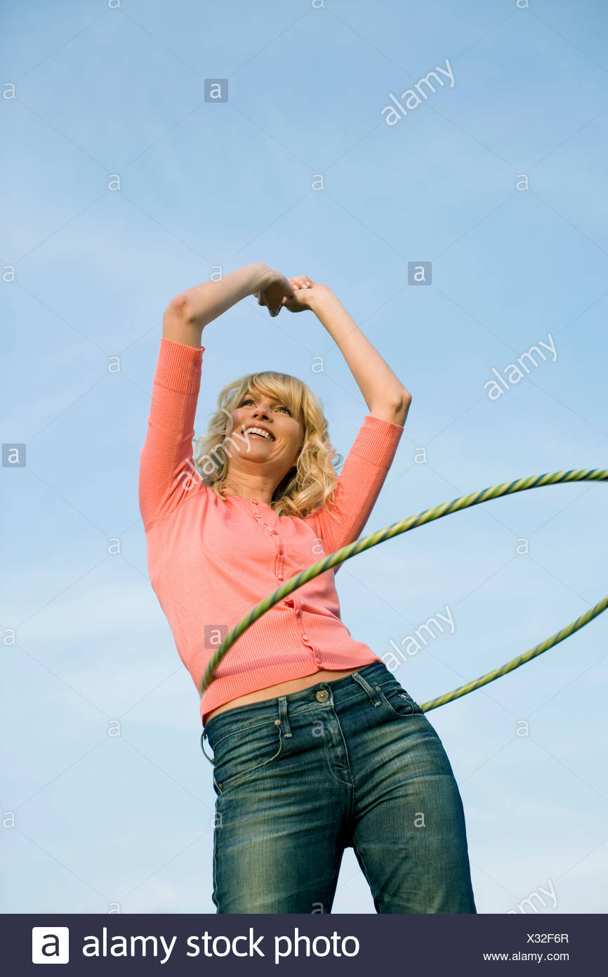 A young woman with a hula hoop around her waist, smiling - Stock Image