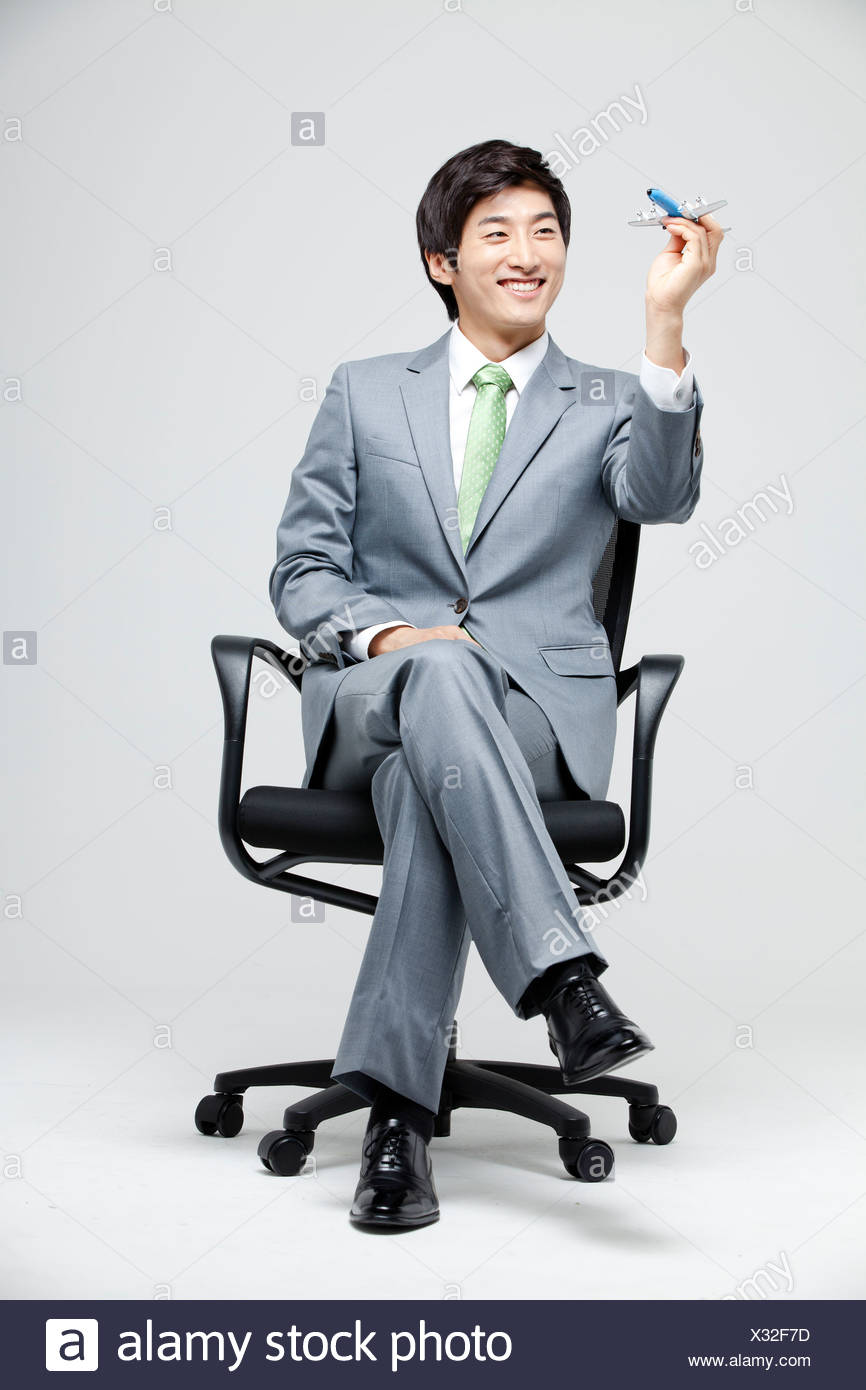 Asian Businessman Holding Model Airplane In Hand - Stock Image