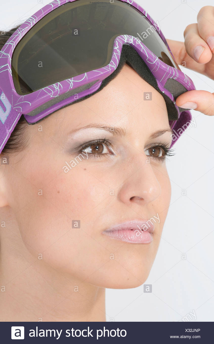 Young woman wearing ski goggles, portrait, close-up - Stock Image