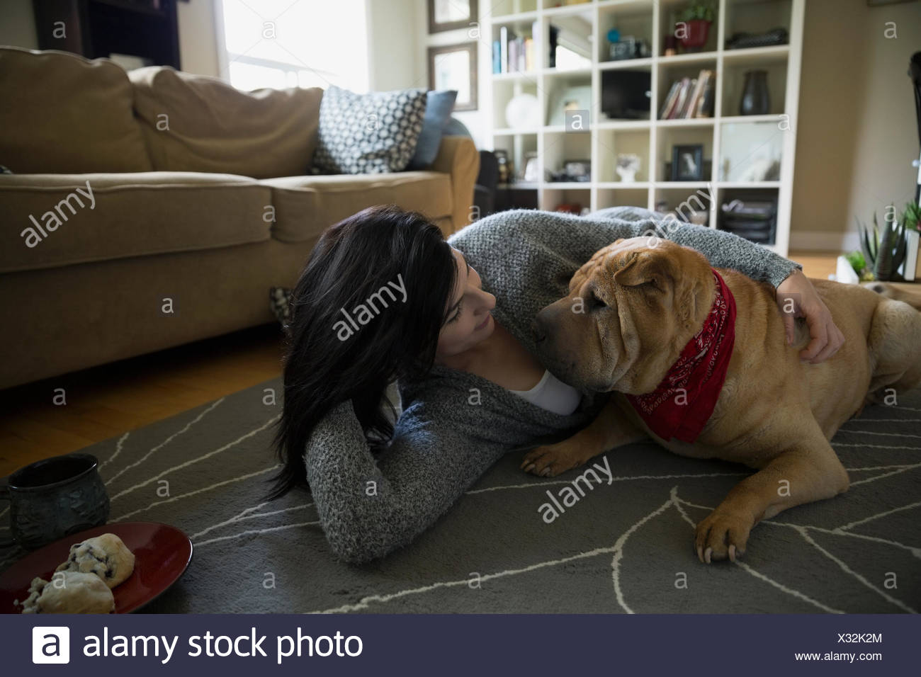 Woman and dog laying face to face floor - Stock Image