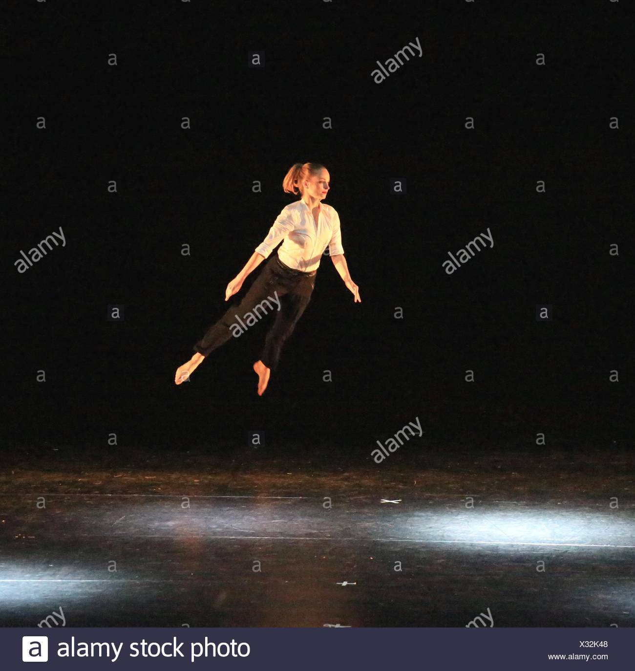 Full Length Of Young Woman Standing Mid Air Against Black Background - Stock Image