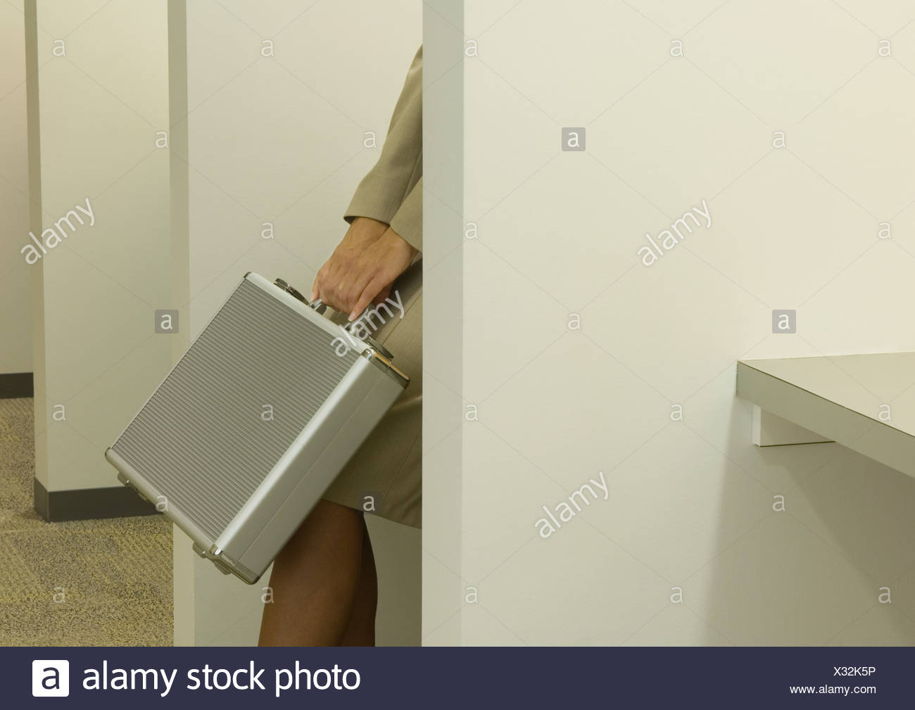 Woman behind partition, holding briefcase over knees, cropped - Stock Image