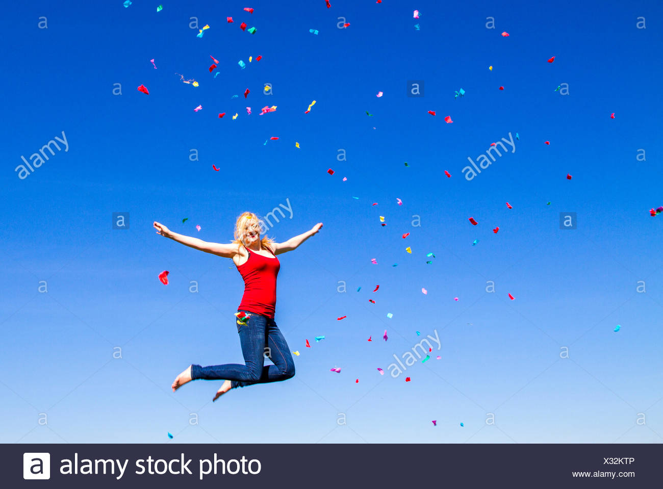 Portrait of blond woman jumping with confetti against blue sky - Stock Image