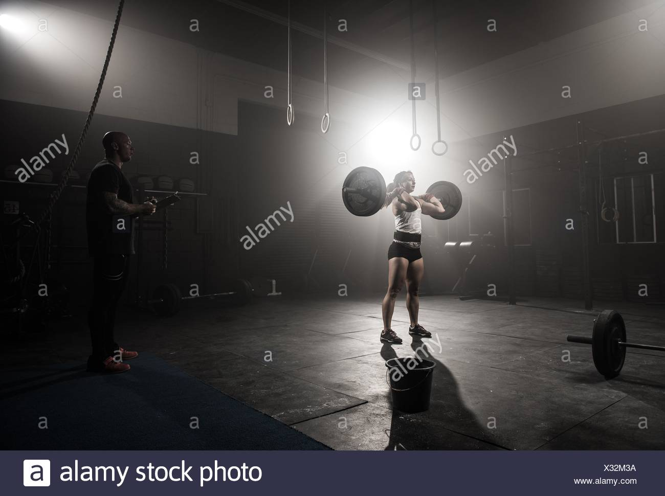 Young woman lifting barbell, while trainer looks on - Stock Image