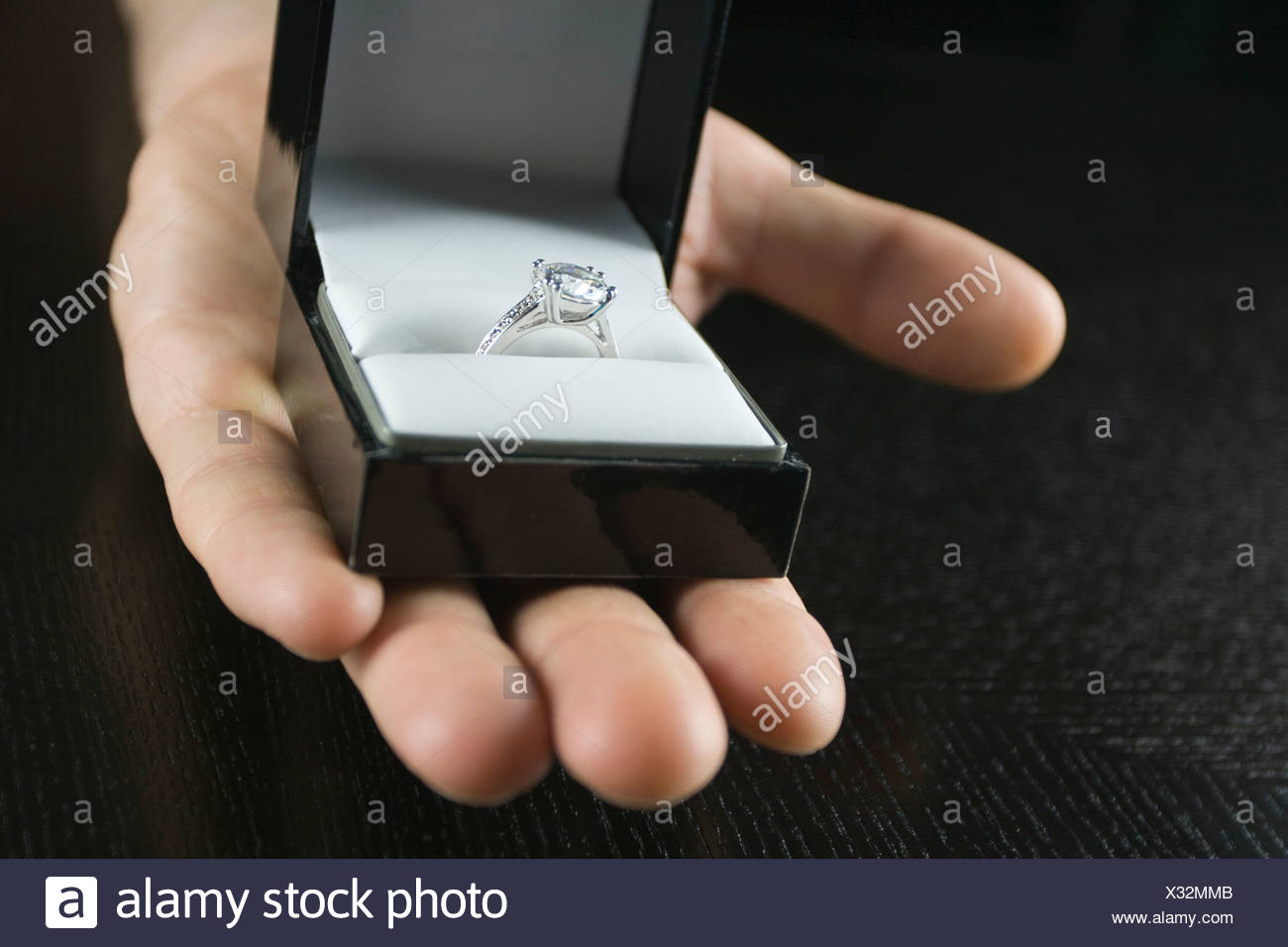 Close up of man's hand holding engagement ring in box - Stock Image