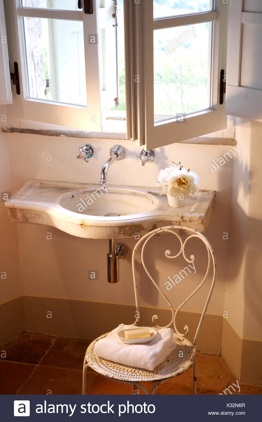 Open Windows Above Small Wall Mounted Basin In Italian Country Bathroom With A White Metal Vintage Chair