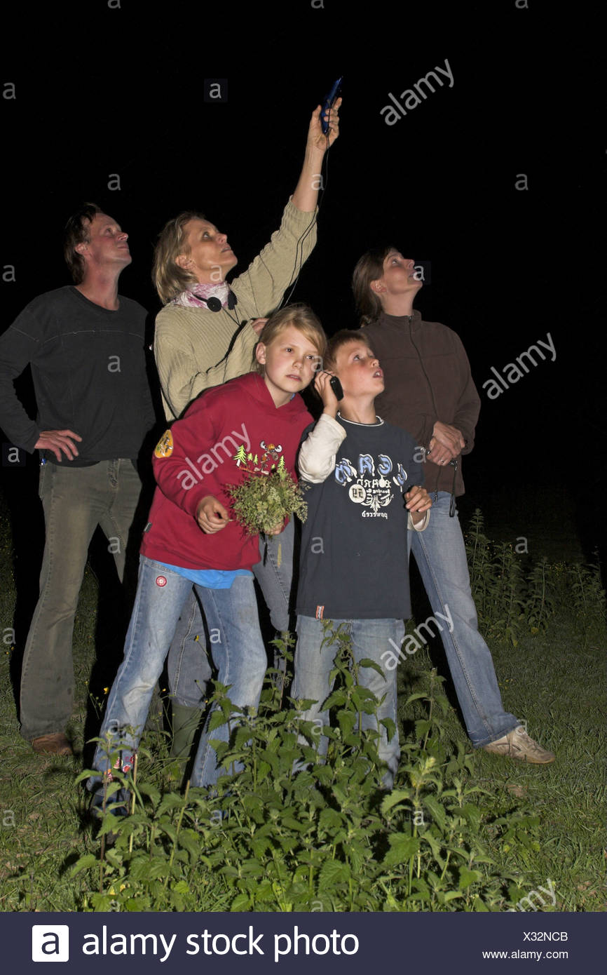 children and adults on a bat-excursion at night, with pocket lamp and bat-detector - Stock Image