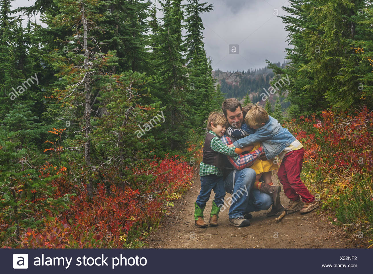 Three children hugging their father - Stock Image