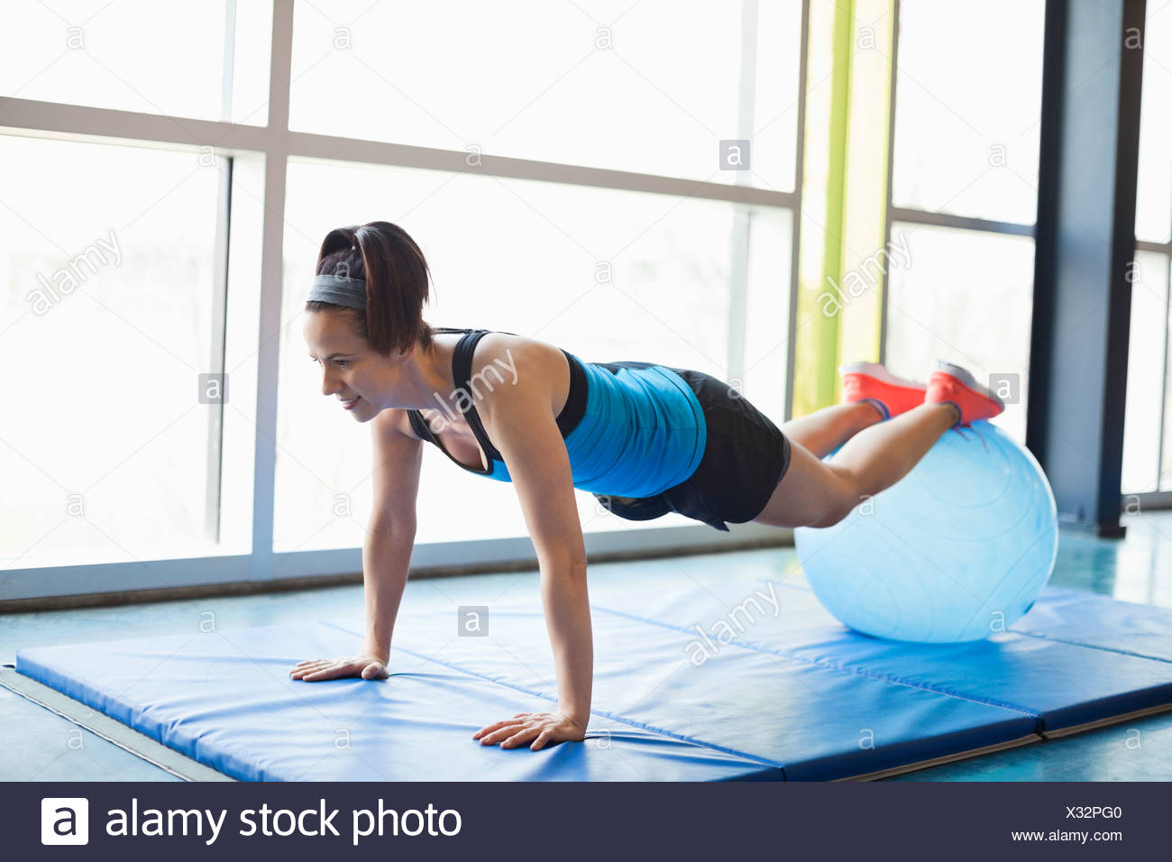 Woman exercising with fitness ball in fitness center - Stock Image
