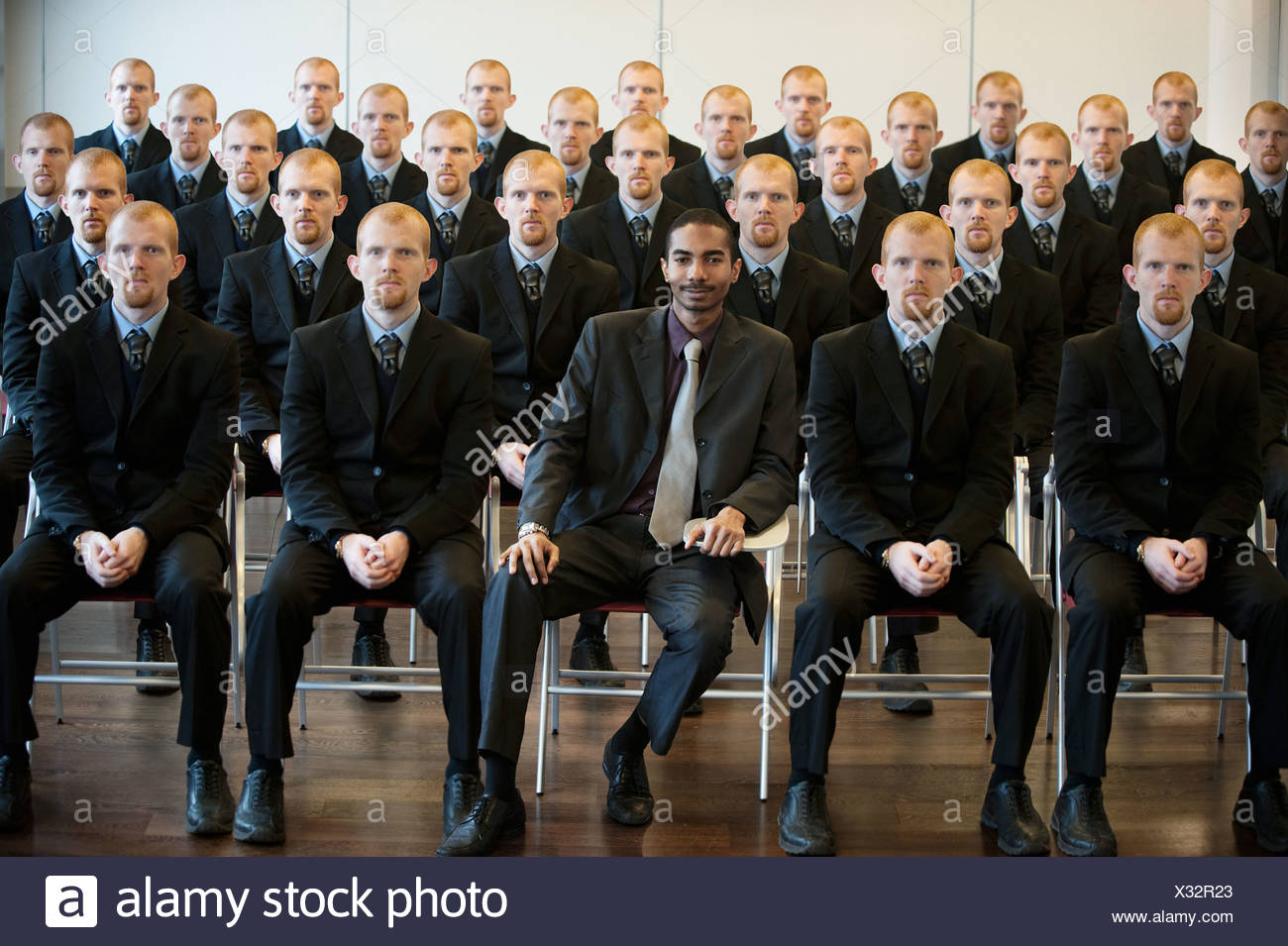 1 black businessman with 25 white clones Stock Photo