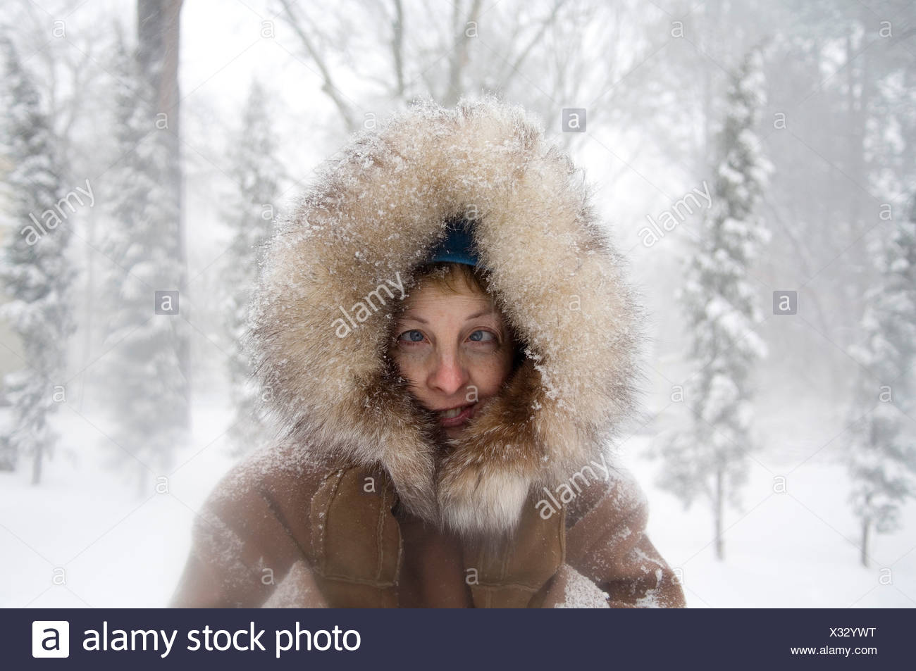 A woman stands outside in a fur-trimmed coat after a snowstorm. - Stock Image