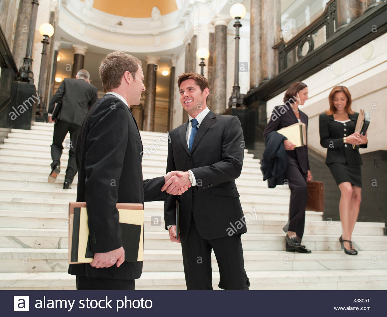 Smiling lawyers shaking hands on stairs - Stock Image