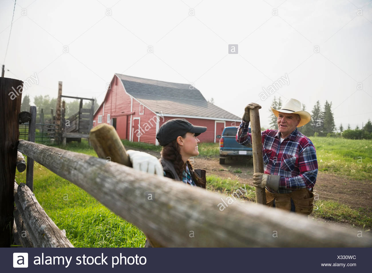 Ranchers with fence posts talking in pasture - Stock Image
