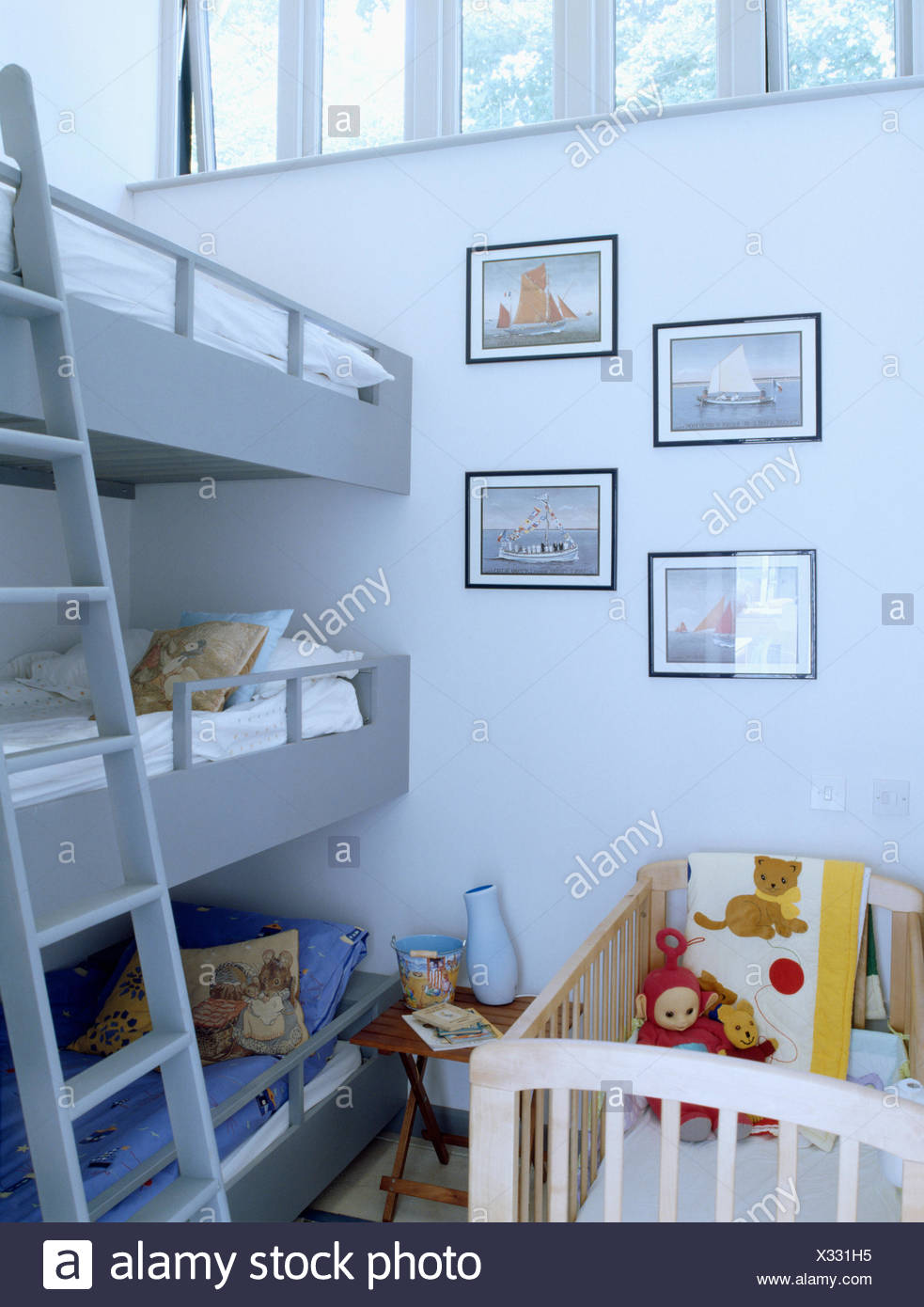 Picture of: Babies Cot And Triple Bunk Beds With Ladder In Children S Modern Bedroom Stock Photo Alamy
