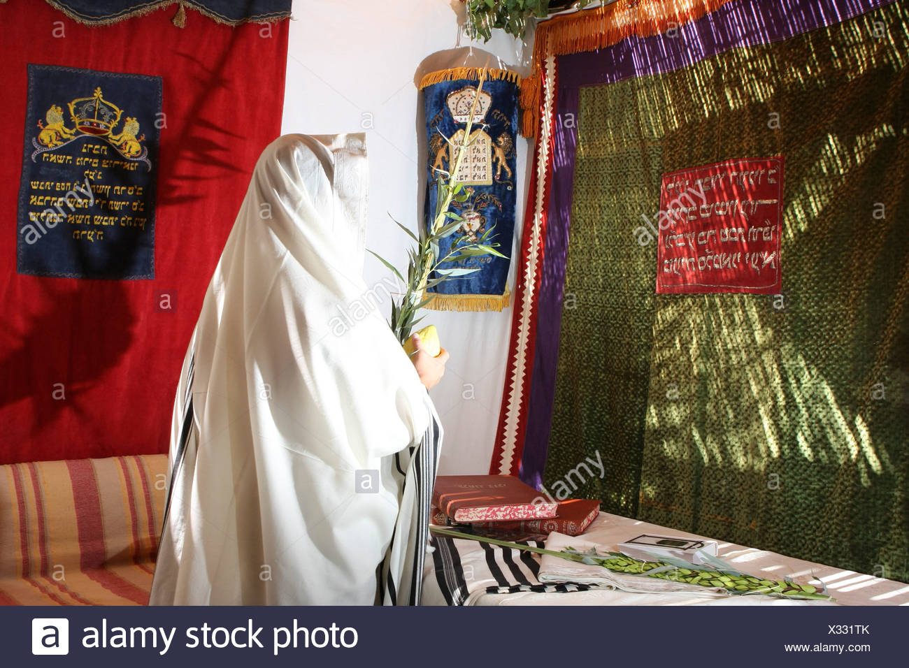Interior of a Sukkah during Sukkoth A man wrapped in a tallith holding the four species - Stock Image