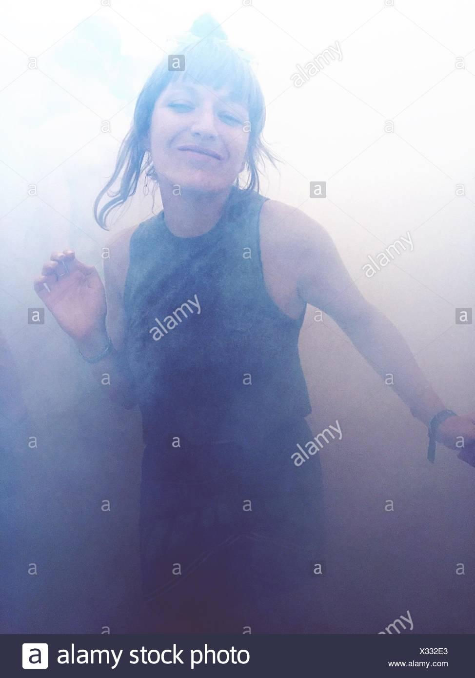 Portrait Of Happy Woman Dancing In Smoke Stock Photo