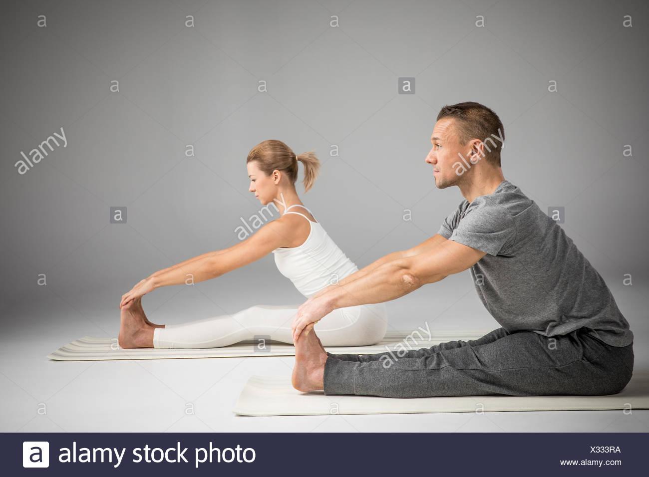 Couple practicing yoga - Stock Image