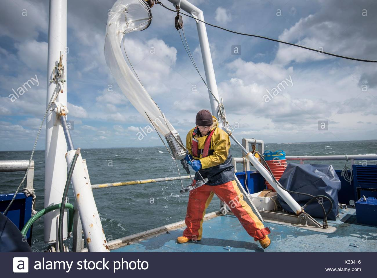 Scientist bringing plankton net on board of research ship - Stock Image