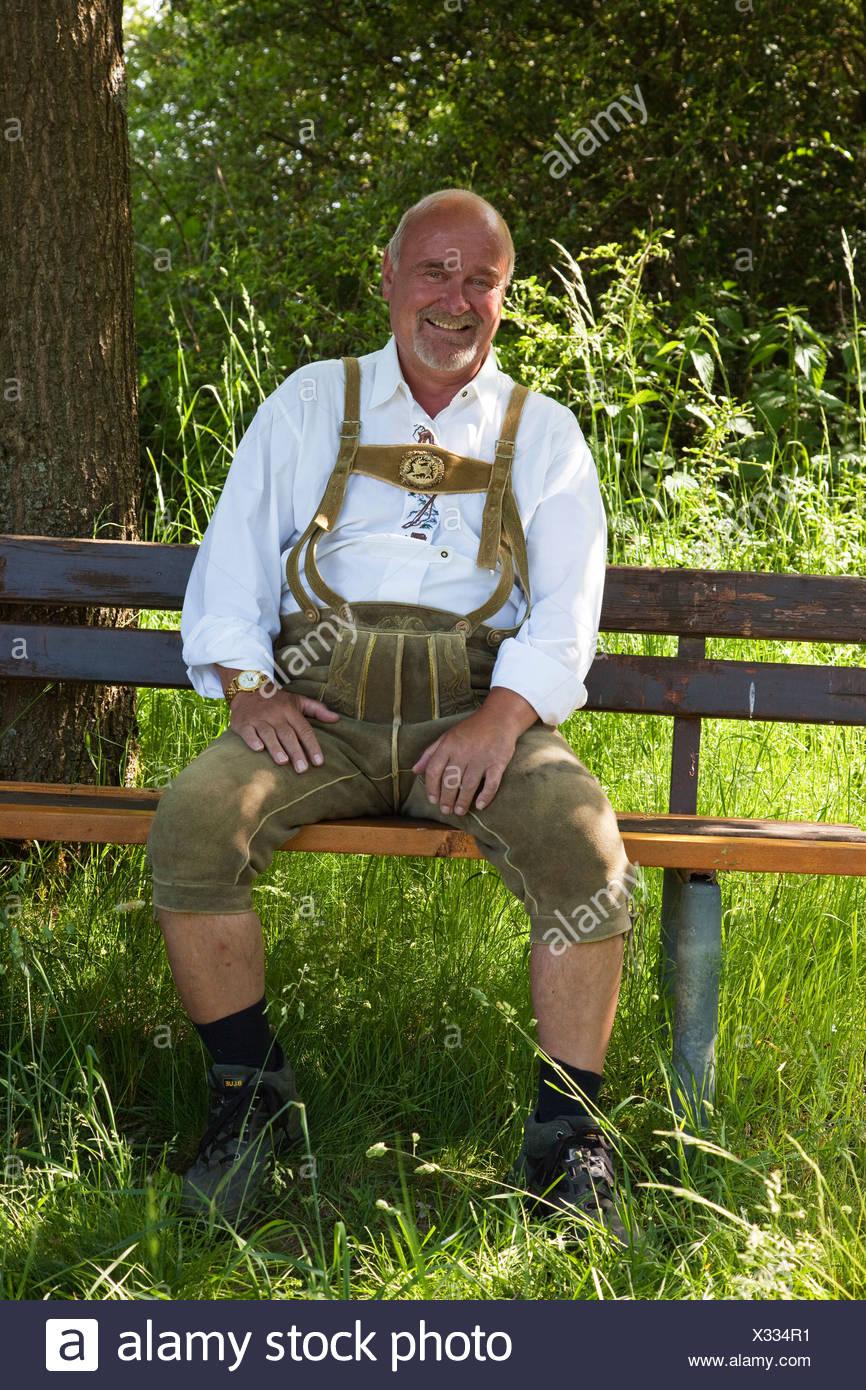 Elderly man wearing traditional Bavarian lederhosen, sitting on a wooden bench in nature - Stock Image