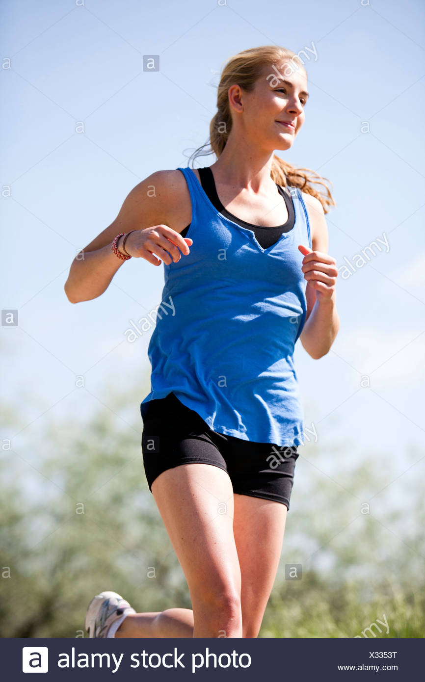 An athletic woman runs along a bike trail on a warm sunny day. - Stock Image