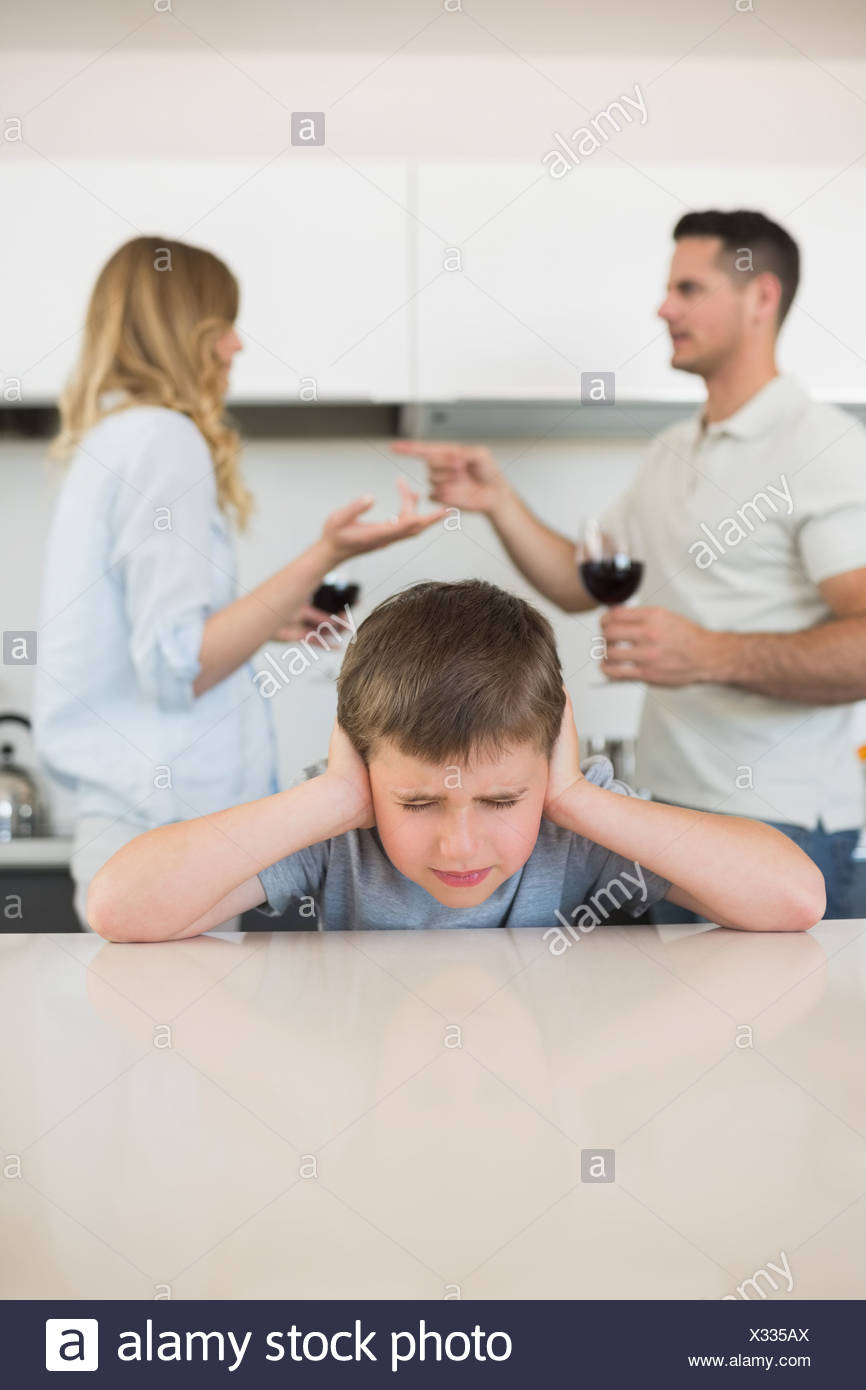 Irritated boy covering ears while parents arguing - Stock Image