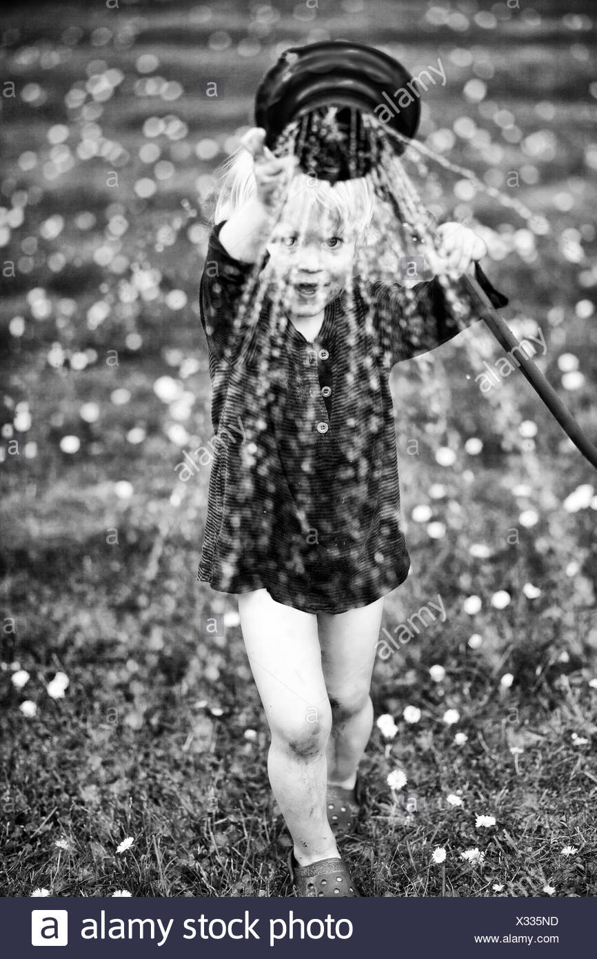 Young boy playing with a watering hose in a garden - Stock Image