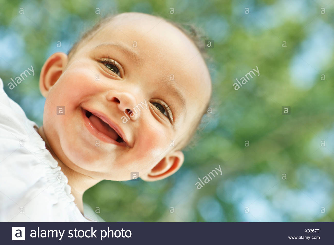 Baby smiling looking down at camera Stock Photo