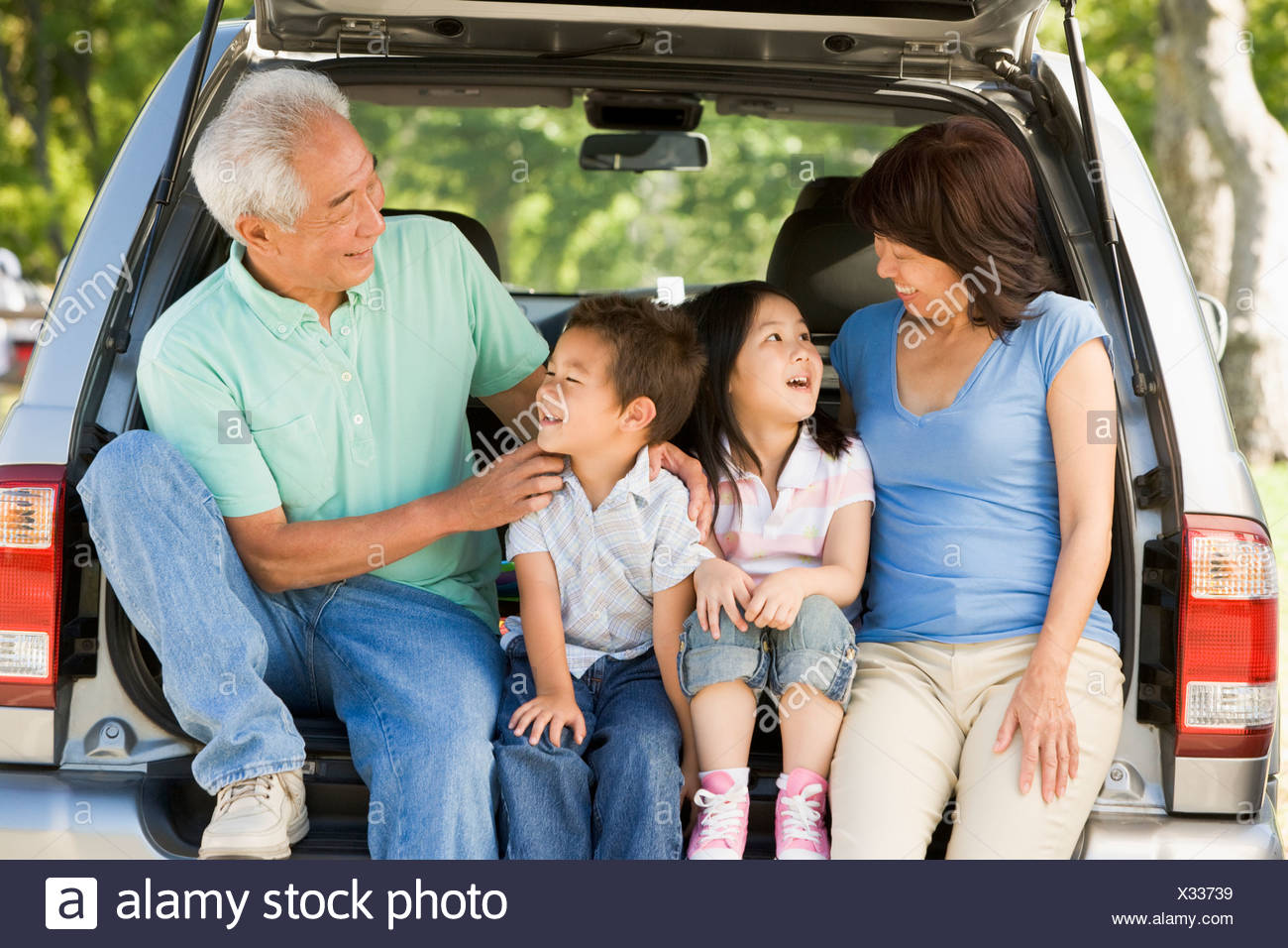 Grandparents with grandkids in tailgate of car - Stock Image