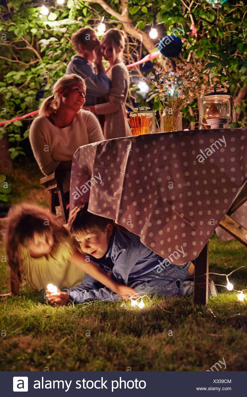 Mischievous kids enjoying garden party at night - Stock Image