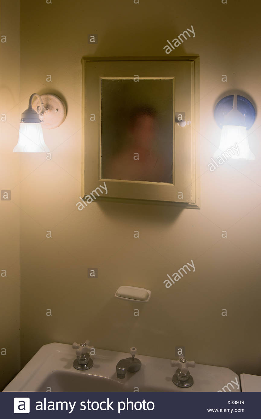 Man confronts his murky image in the mirror. - Stock Image