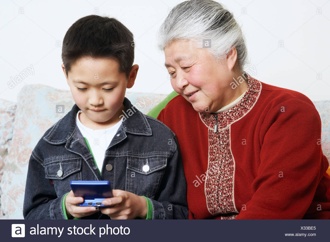 Close-up of a boy and his grandmother playing a video game - Stock Image