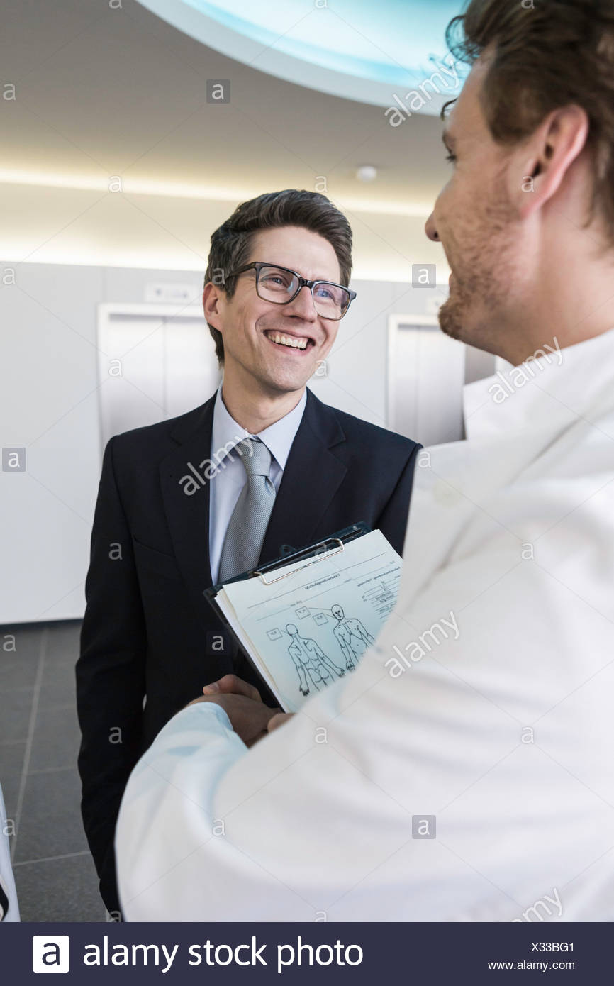 Man wearing lab coat, holding clipboard shaking hands with man wearing business attire - Stock Image