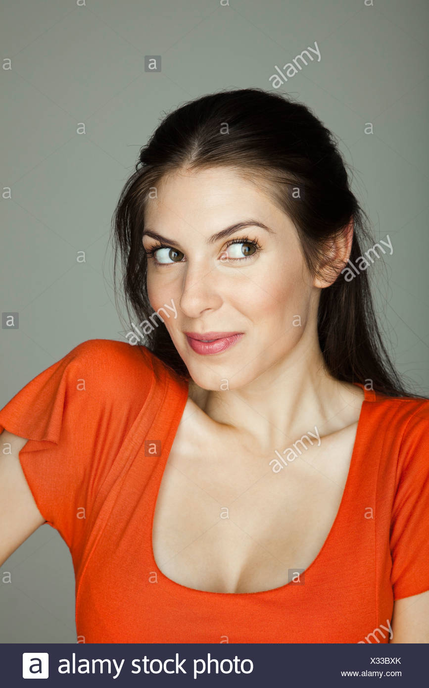 Young woman looking away mischievously - Stock Image