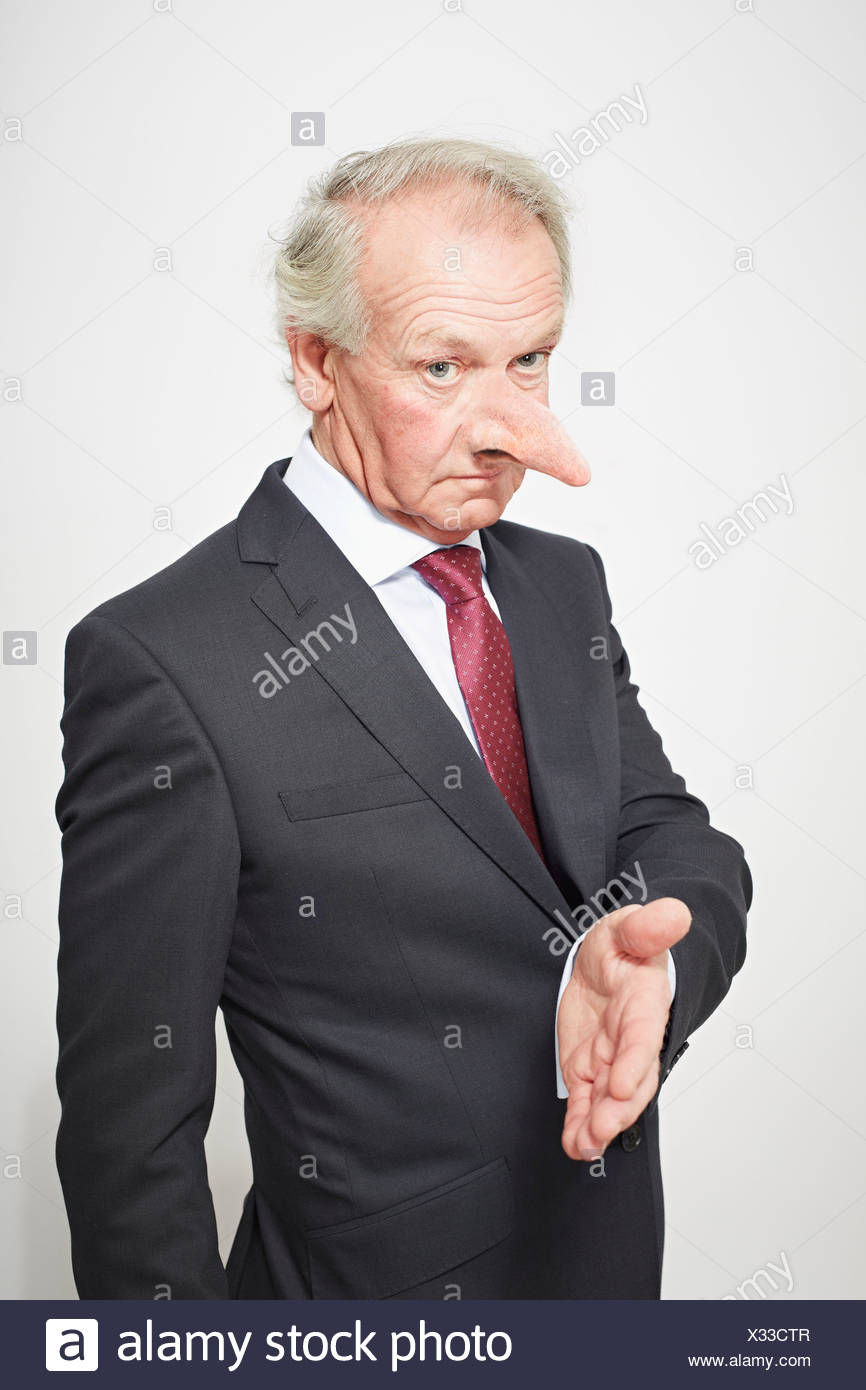 Businessman with long nose offering hand - Stock Image