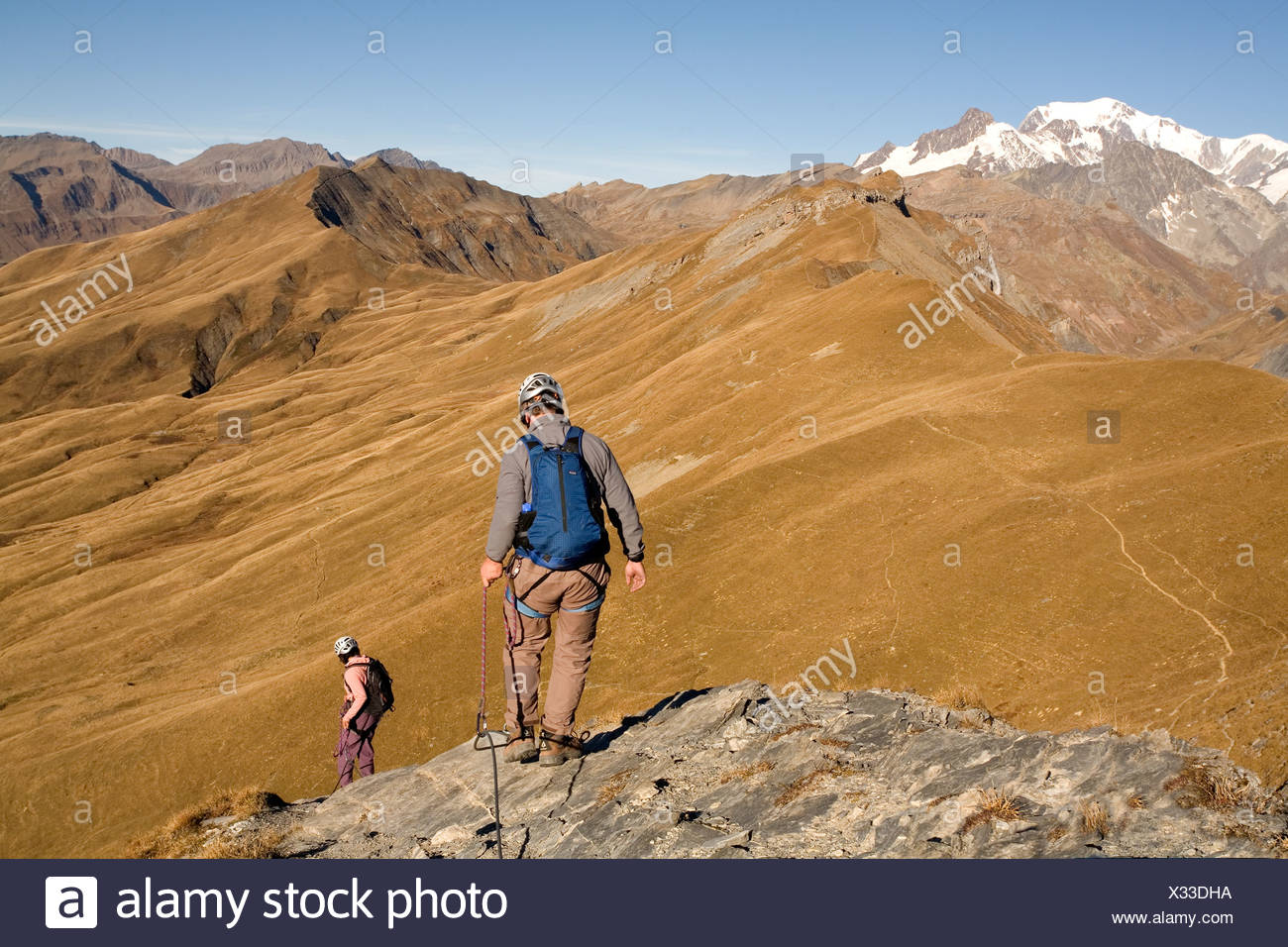 Two people descending a cliff while engaging in the sport of Via Ferrata in the French Alps. - Stock Image