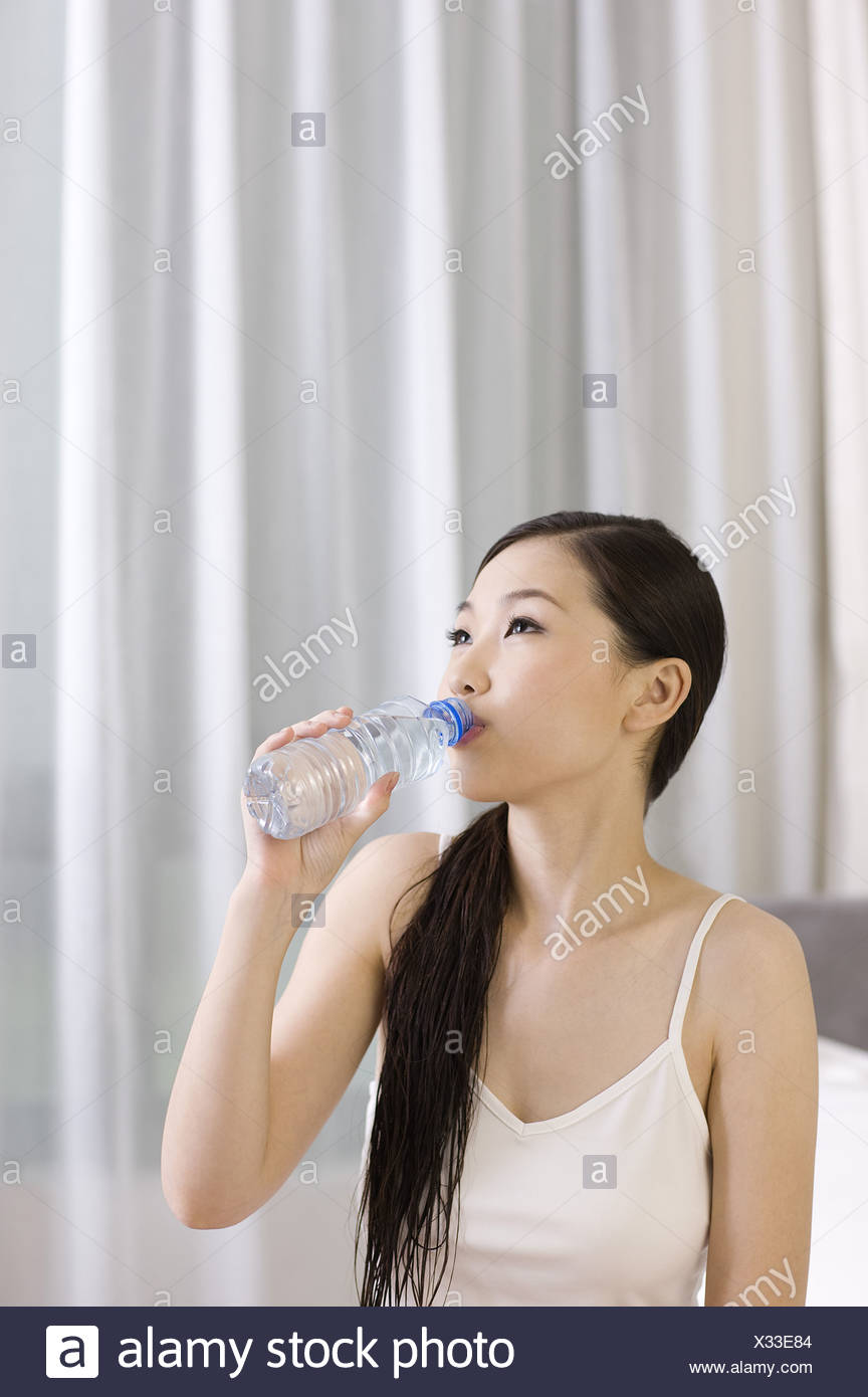 Young woman drinking water and looking away - Stock Image