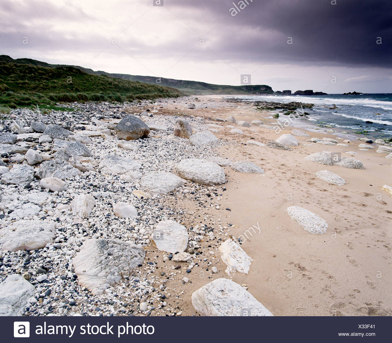 A moody sky overlooks the rocky beach of White Park Bay, N.Ireland - Stock Image