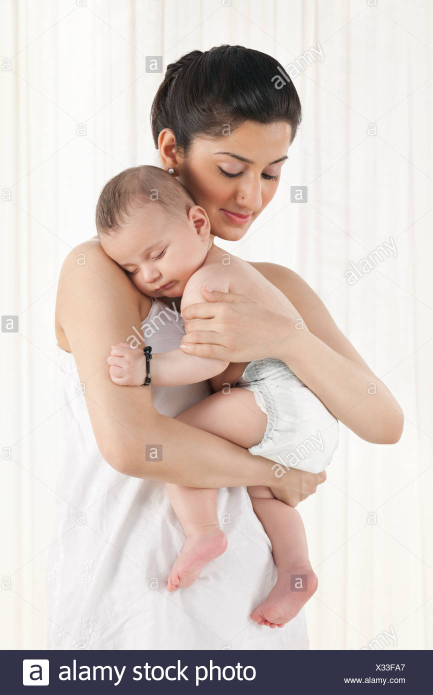 Mother holding a sleeping baby - Stock Image