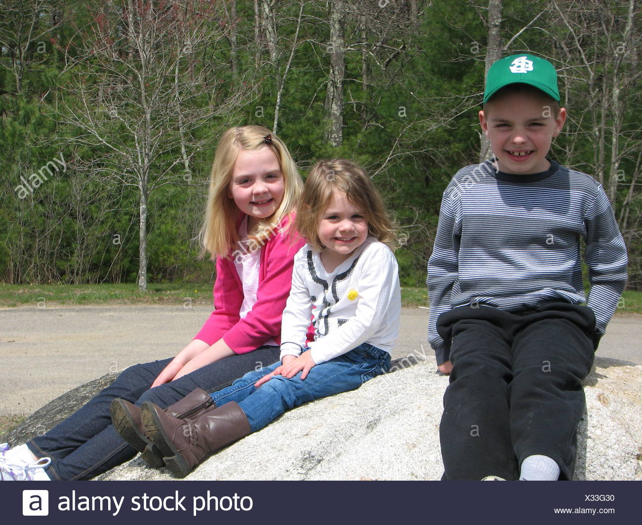 Three smiling children (8-9, 2-3, 6-7) sitting on boulder - Stock Image