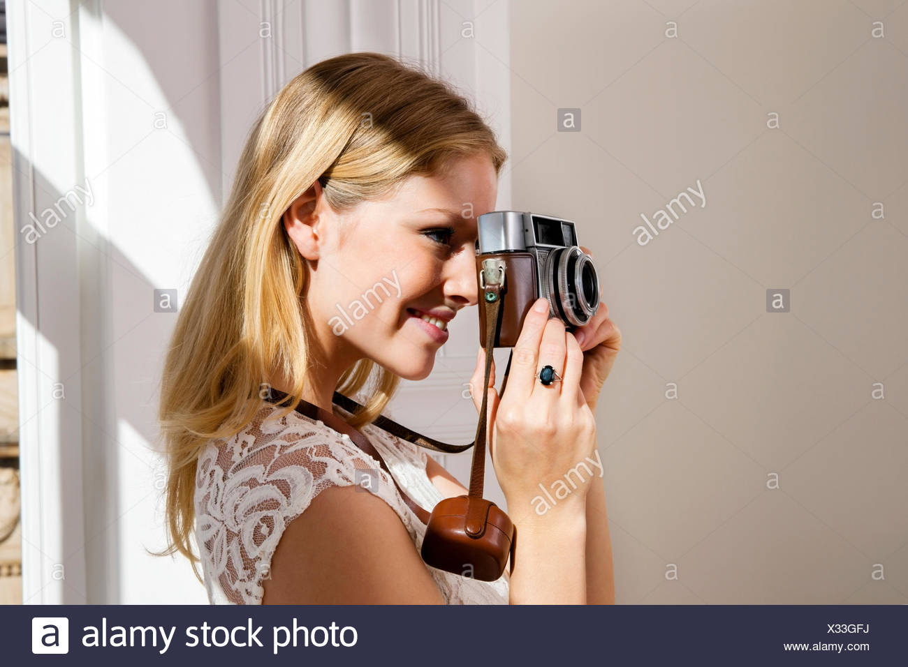 Smiling young woman taking picture with old camera - Stock Image