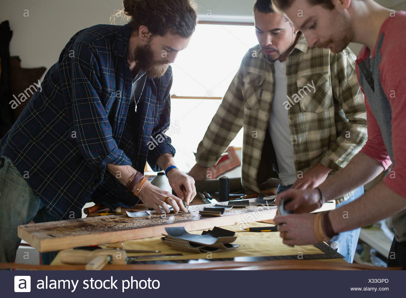Male colleagues making leather belts at workshop - Stock Image
