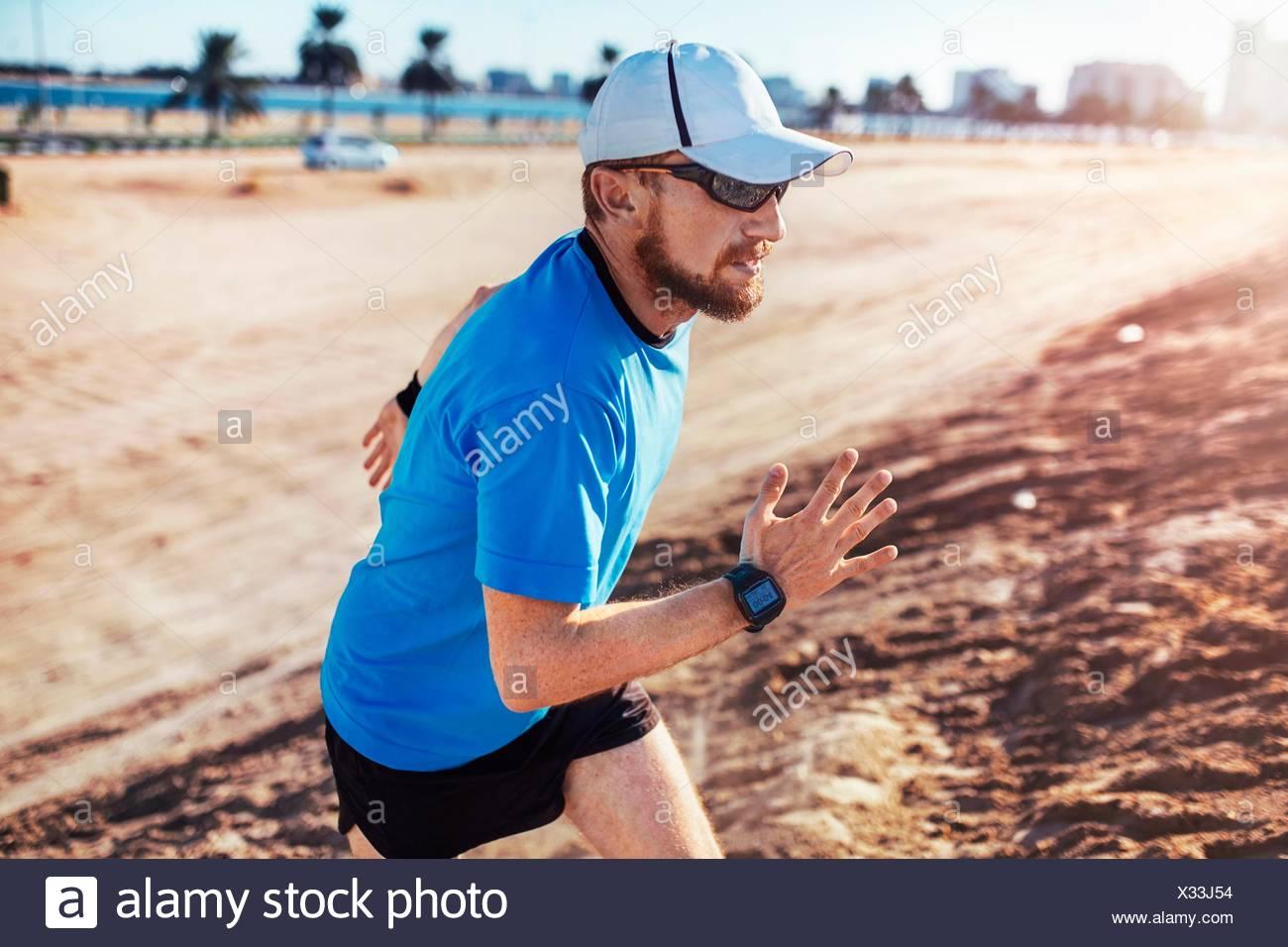 Mid adult man wearing baseball cap running up sand dune, Dubai, United Arab Emirates - Stock Image