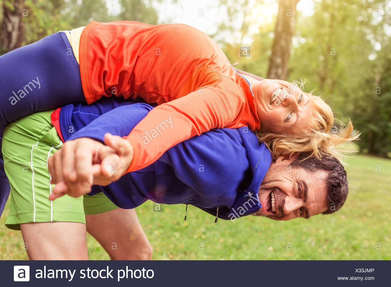 Couple exercising, man stretching woman on back, outdoors, laughing - Stock Image