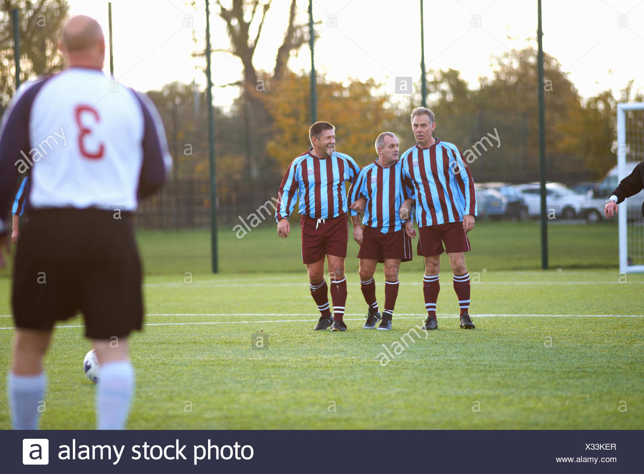 Football players forming wall to defend free kick - Stock Image