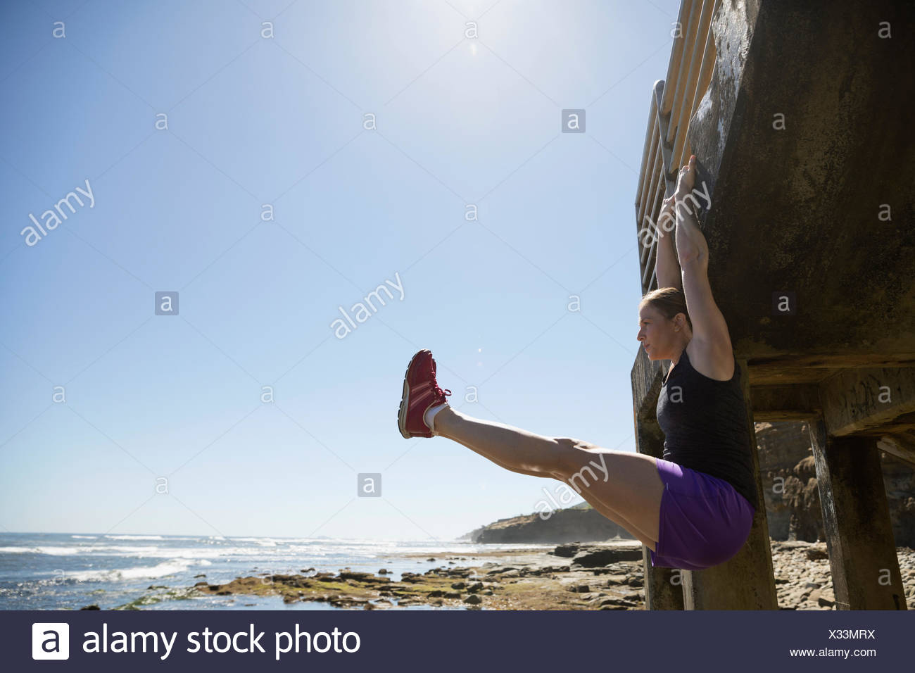Woman exercising, hanging from stairs doing leg lifts along sunny ocean - Stock Image