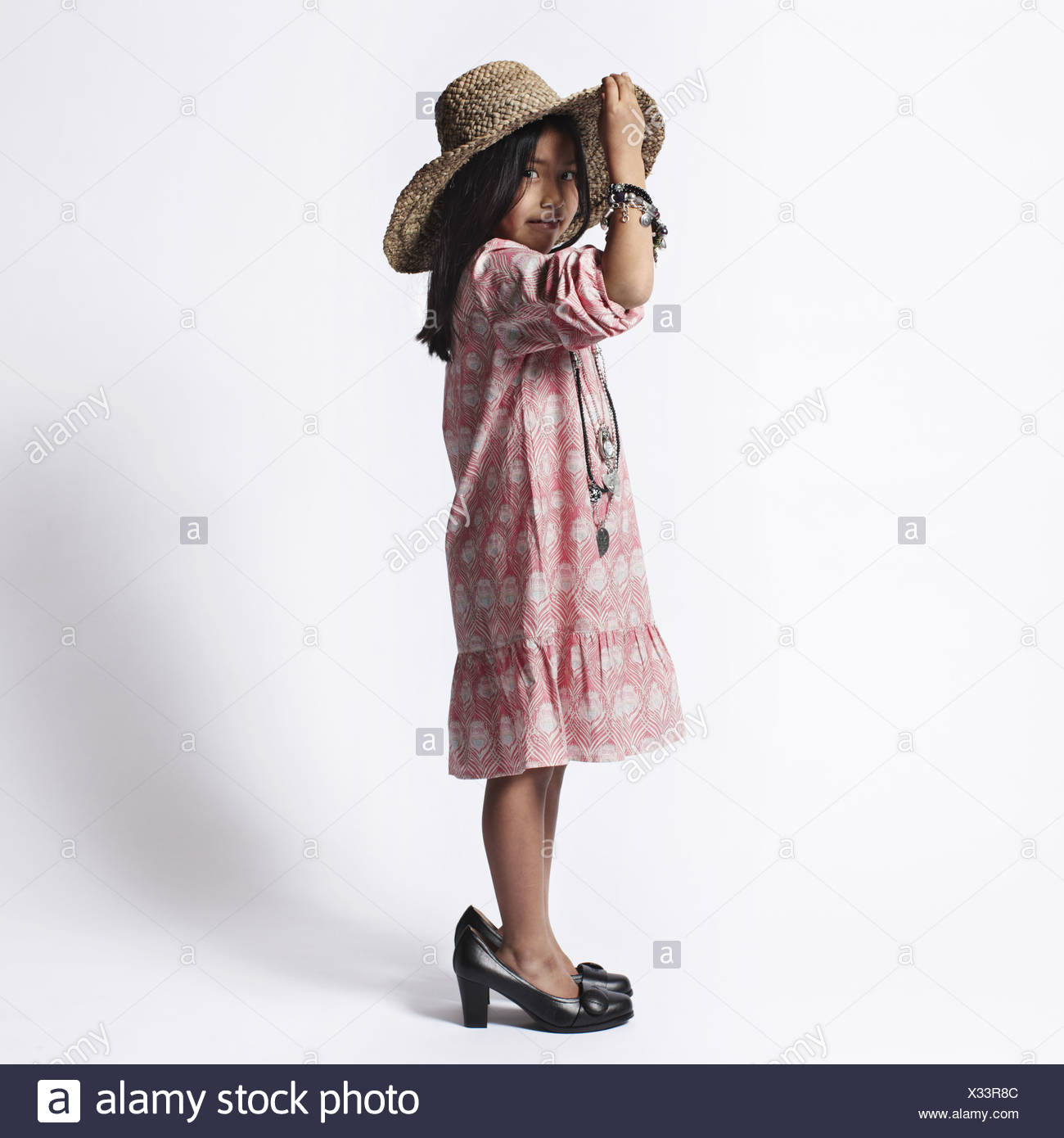 Girl dressing up in mothers shoes - Stock Image