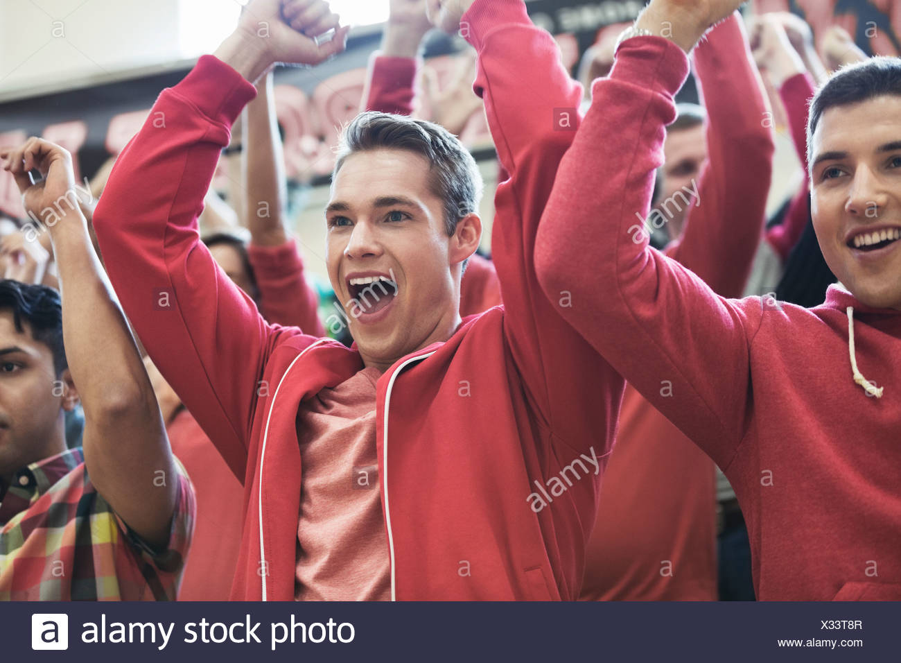Group of students cheering at college sporting event - Stock Image