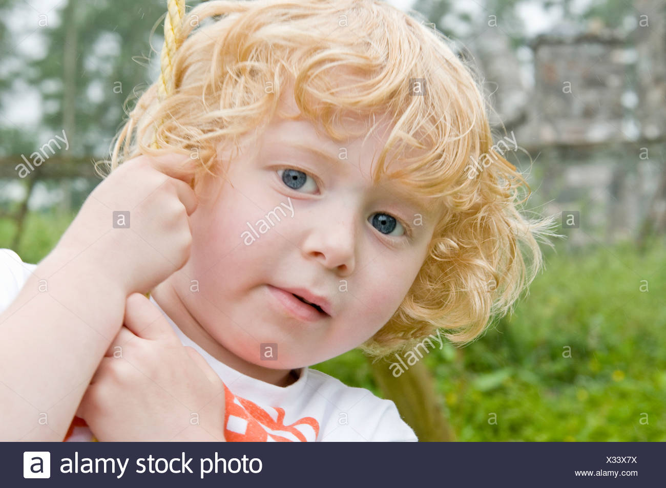 Curly haired boy on swing looking - Stock Image