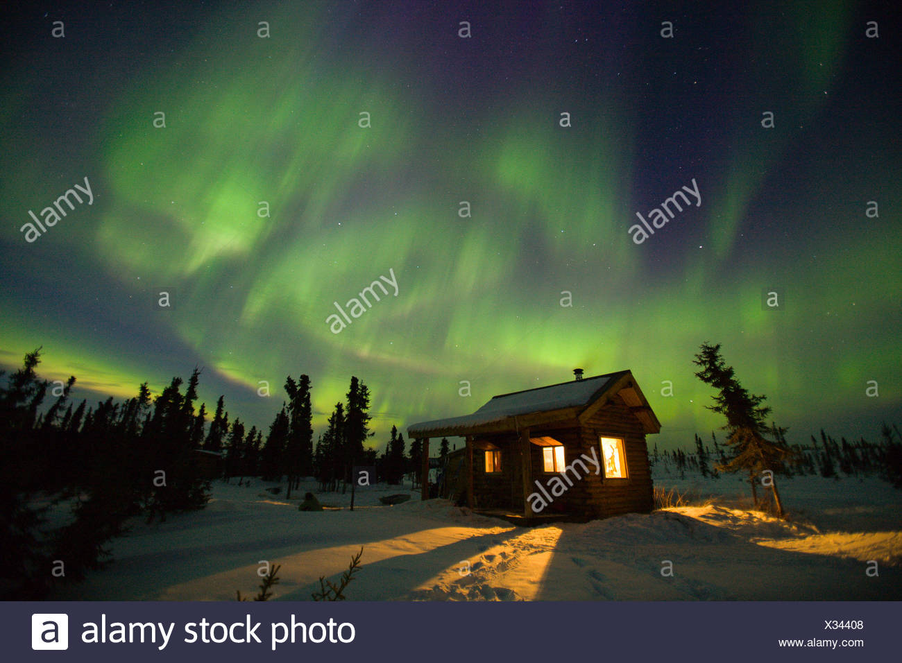 Curtains of green and purple aurora borealis (northern lights) dance over a warm cabin in the hills near Fairbanks, Alaska - Stock Image