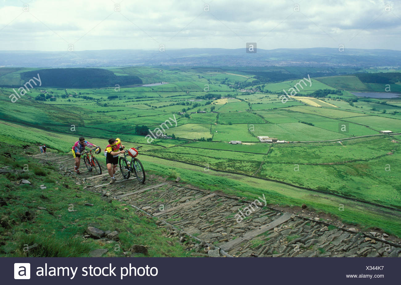 Cyclists pushing their mountain bikes up step ascent of Pendle Hill Lancashire UK - Stock Image